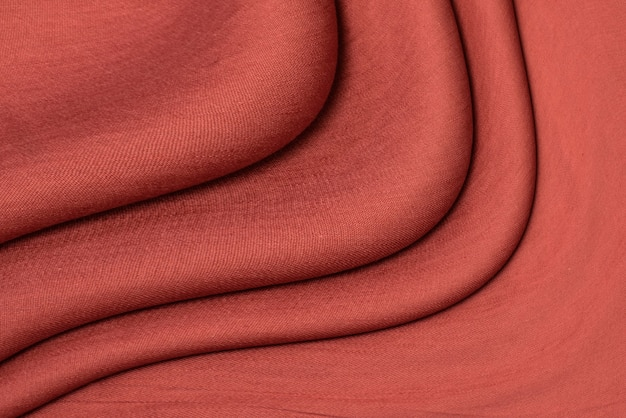 The texture of red linen fabric of dark red color close-up. textured abstract red background, top view
