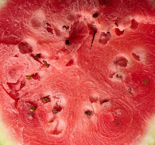 Texture of ripe red watermelon with brown seeds, full frame, close up
