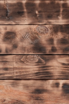 The texture of the scorched wooden wall. wall of smooth orange long wooden boards with a specific black texture of frying