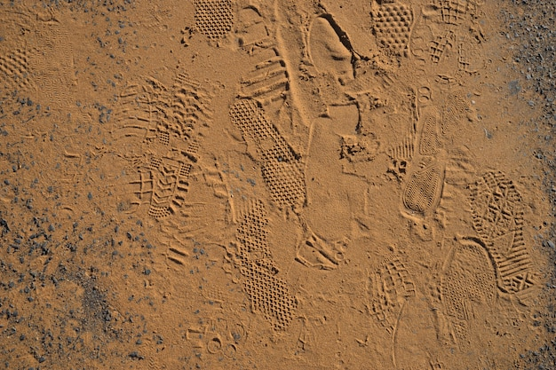 Texture of shoes foot prints on golden sand background