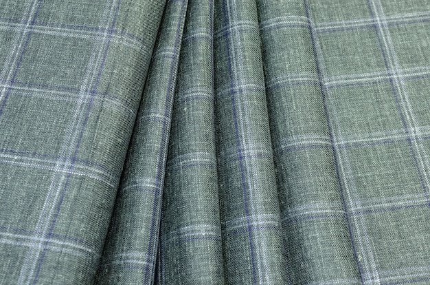 The texture of the silk fabric in a light green-blue check. background, pattern