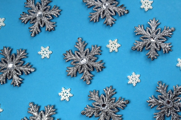Texture of silver snowflakes on a blue background.