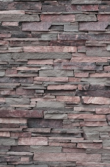 Texture of a stone wall from long and rough stones of different sizes and tones