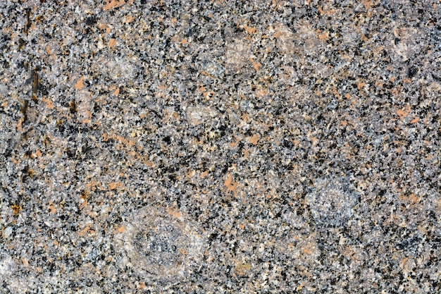 Texture of stones on road closeup. part of a road paved with square stones of red granite.