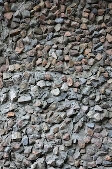 The texture of a strong stone wall of many concreted stones of various shapes