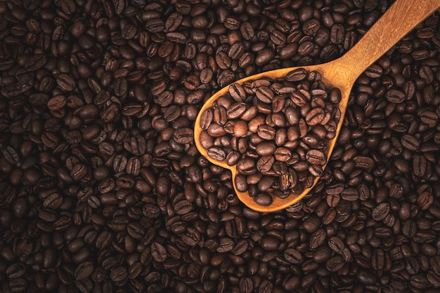 Texture surface pattern background of roasted coffee beans and heart wooden spoon