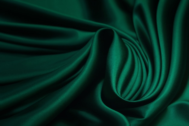 Текстура, текстура зеленой шелковой ткани. красивая изумрудно-зеленая мягкая шелковая ткань.
