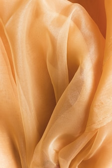 Texture of transparent pastel orange crumpled fabric