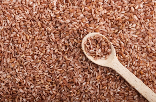 Texture of unpolished brown rice with wooden spoon. top view, close up.