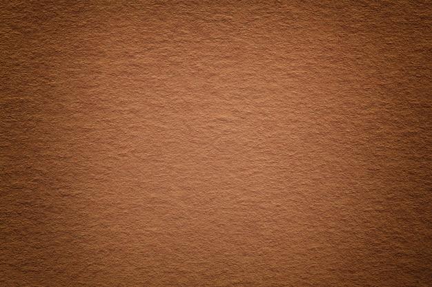 Texture of vintage dark bronze paper background with vignette. structure of dense light brown kraft cardboard with frame. felt rusty gradient backdrop closeup.