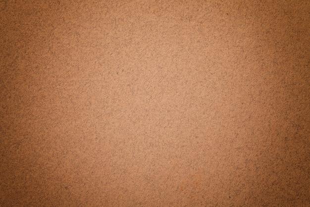 Texture of vintage dark brown paper background with matte vignette. structure of dense bronze kraft cardboard.