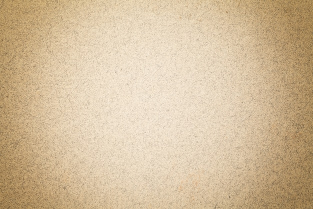 Texture of vintage light brown paper background with matte vignette. structure of beige kraft cardboard with frame.