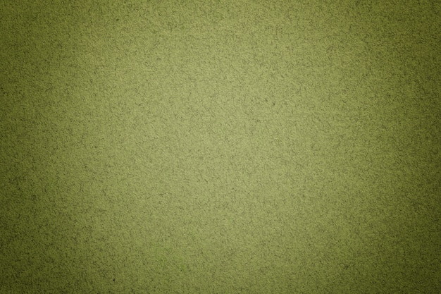 Texture of vintage light green paper background with matte vignette. structure of olive kraft cardboard with frame.