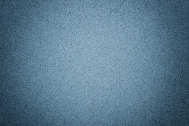 Texture of vintage navy blue paper background with matte vignette. structure of denim kraft cardboard with frame.