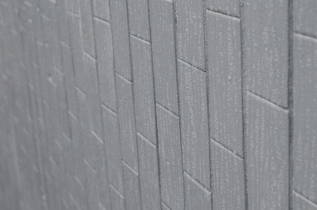 The texture of the wall from the old tile painted gray under the influence of condensation