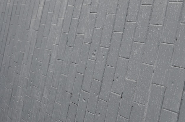 The texture of the wall from the old tile, painted gray under the influence of condensation