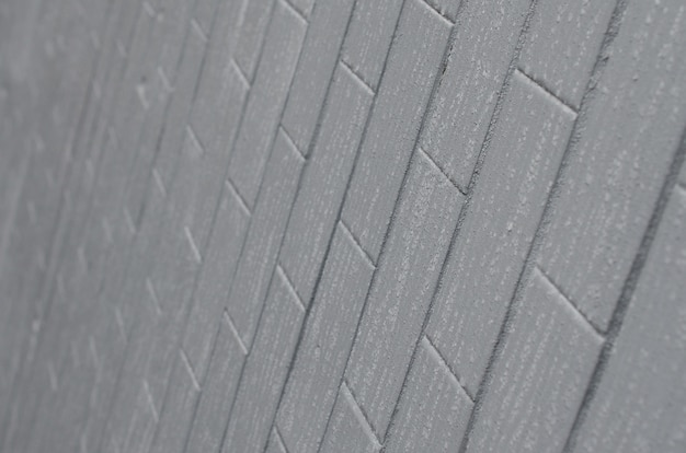 The texture of the wall from the old tile, painted gray under the influence of condensation.