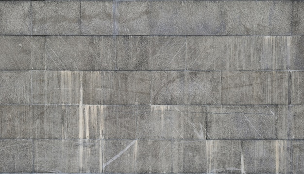 The texture of a wall of large granite tiles that are covered