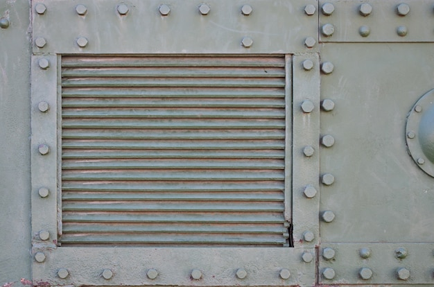 The texture of the wall of the tank, made of metal and reinforced with a multitude of bolts and rivets.