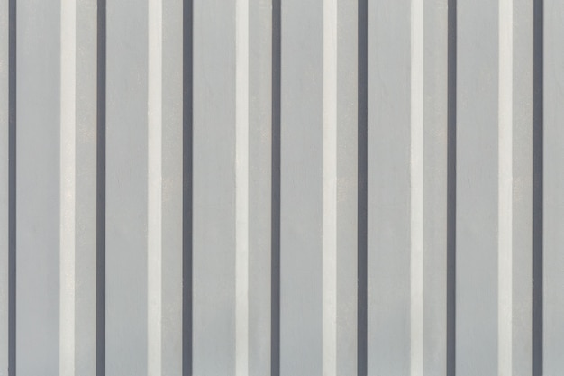 Texture of the wall with gray vertical siding panels in strips with copy space