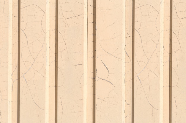 Texture of the wall with siding panels is painted yellow with lots of small cracks from time.