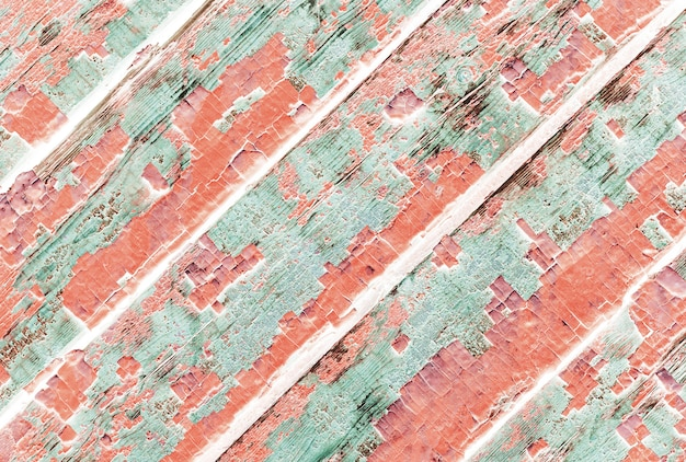 Texture of weathered wooden lining boards with peeling violet paint and rusty nail heads