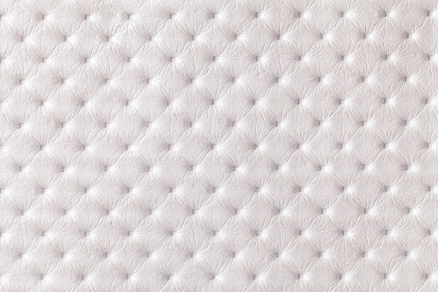 Texture of white leather background with capitone pattern, macro. pearl textile of retro chesterfield style. vintage fabric.