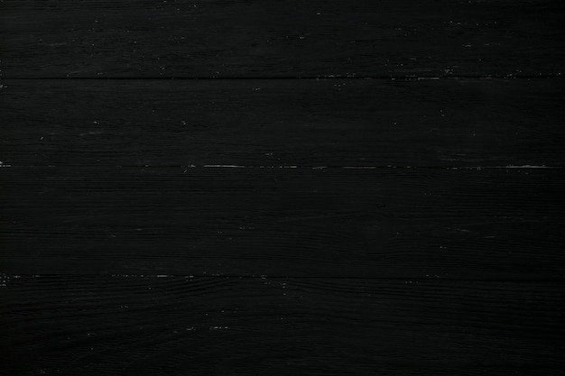 The texture of the wooden background is black, located horizontally, closeup.