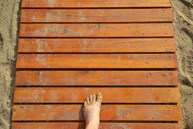 Texture of wooden boards with sand and a foot