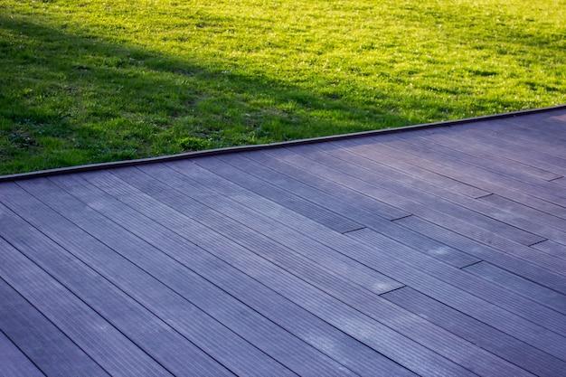 Texture of wooden outdoor floor with green grass