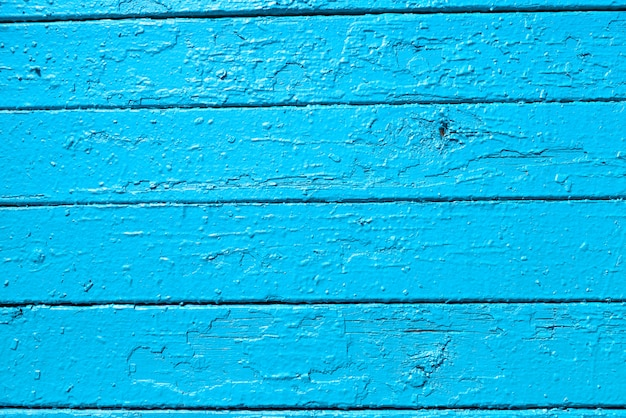The texture of wooden planks, painted with light blue paint, locally peeled.