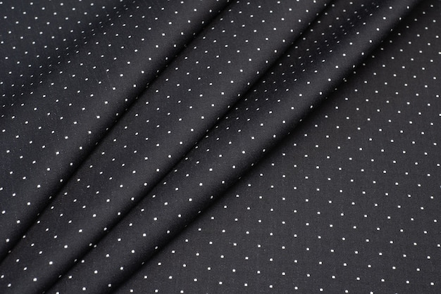 The texture of the wool fabric is black with white dots.