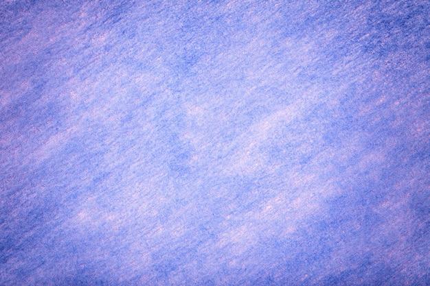 Texture of woolen matt violet textile light blue background of felt fabric.