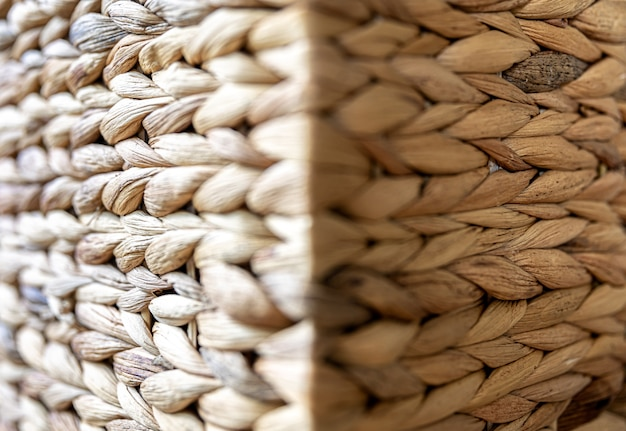 Texture of woven beige straw, background of braids from the plant stem close-up.