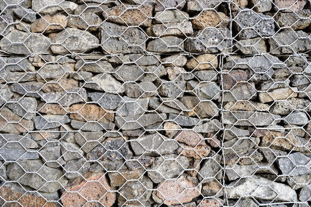 Textured background of gabion, rock wall with wire meshed fence.