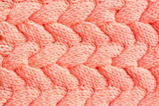 テクスチャ背景。絡み合った三つ編みの形をした桃色のニット生地
