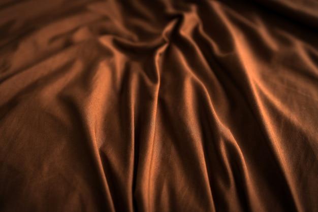Текстурированный фон из коричневой клетчатой ткани со складками. фото высокого качества
