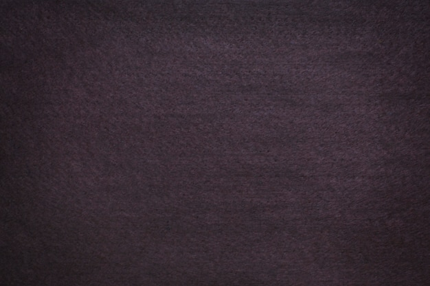 Текстурированный фон темно-коричневого фетра с виньеткой