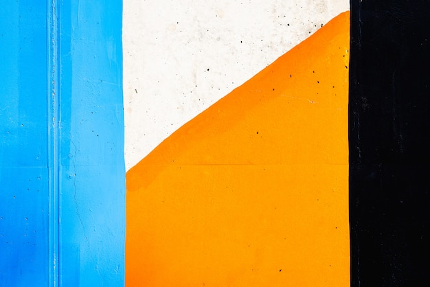 Textured background of a wall painted with black, orange and white lines.