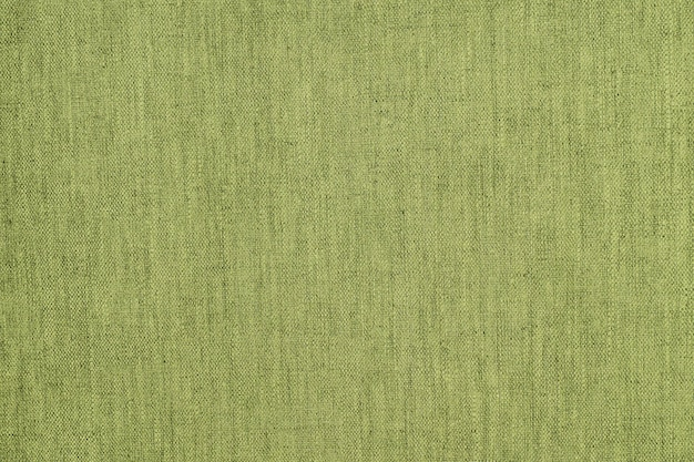 Textured background or wallpaper from the rough fabric of green lime color