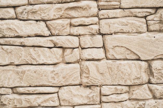 レンガの粒子でテクスチャ背景に亀裂や継ぎ目のある材料の壁の壁