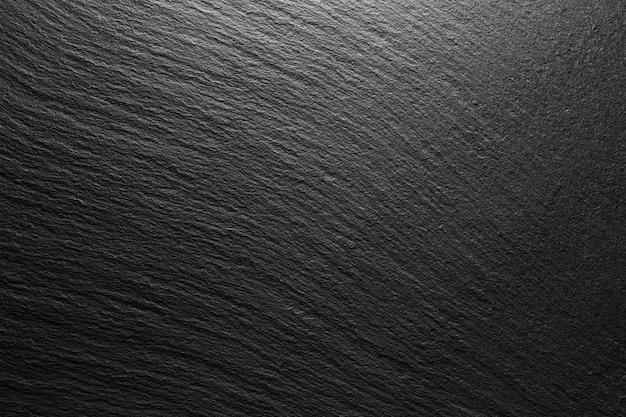 光のスポットとテクスチャの黒いスレートの背景