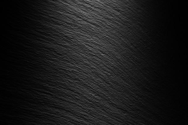Текстурированный черный шиферный фон с пятном света