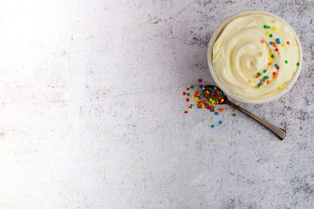 Textured butter cream in a bowl with spoon and sprinkles.
