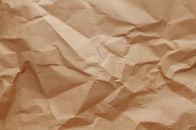 Текстурированная скомканная упаковка на коричневом бумажном фоне.