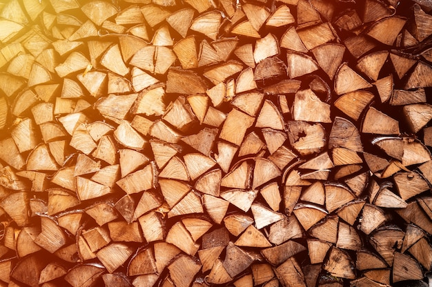 Textured firewood background of chopped wood for kindling and heating the house. a woodpile with stacked firewood. the texture of the birch tree. flare