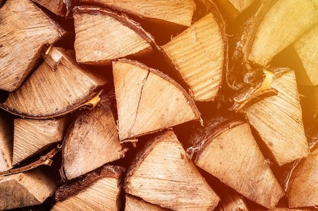 Текстурированный фон дров из рубленых дров для растопки и отопления дома. поленница со сложенными дровами. текстура березы. вспышка