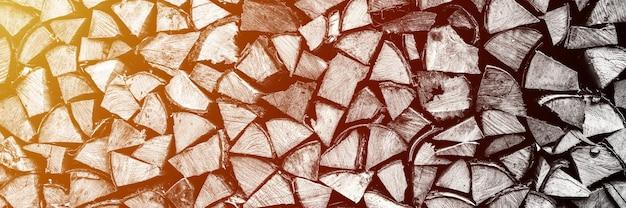 Текстурированный фон дров из рубленых дров для растопки и отопления дома. поленница со сложенными дровами. текстура березы. тонирован в черный белый или серый цвет. баннер. вспышка