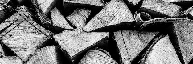Текстурированный фон дров из рубленых дров для растопки и отопления дома. поленница со сложенными дровами. текстура березы. тонирован в черный белый или серый цвет. знамя