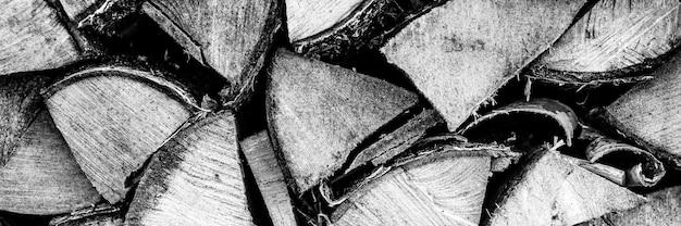 家を燃やし、暖房するための刻んだ木のテクスチャード薪の背景。薪を積み上げたウッドパイル。白樺の木の質感。ブラックホワイトまたはグレーの色調。バナー